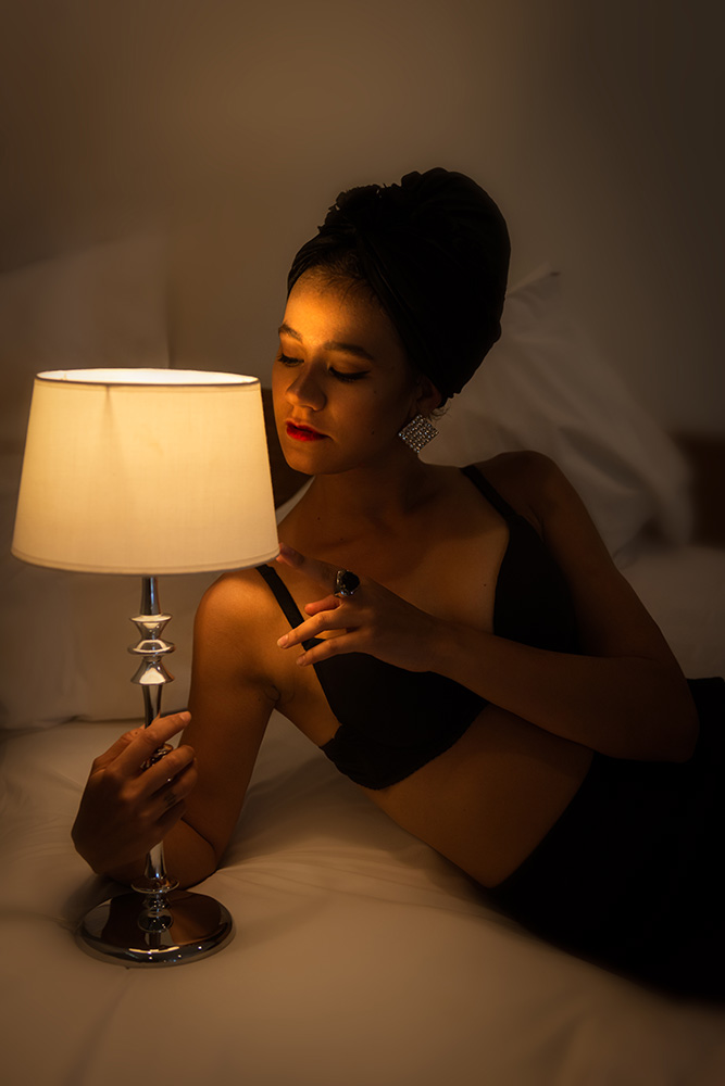 Elegant woman holding a lamp facing the lamp