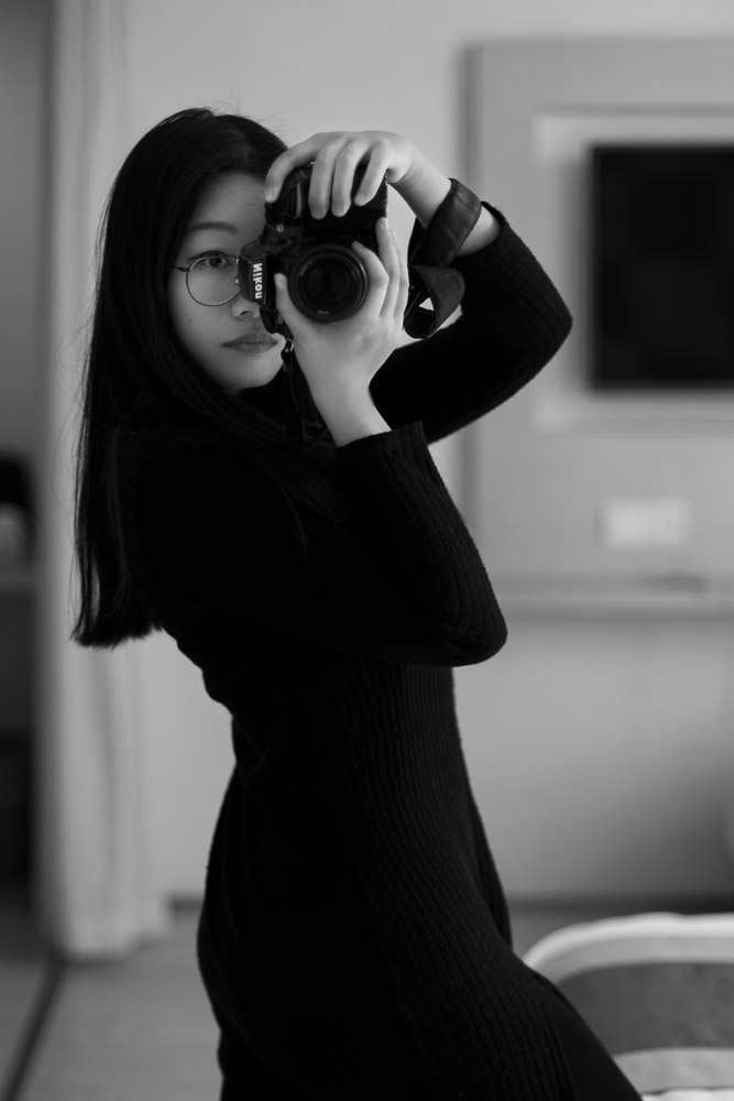 Female boudoir photographer holding a camera in front of a mirror